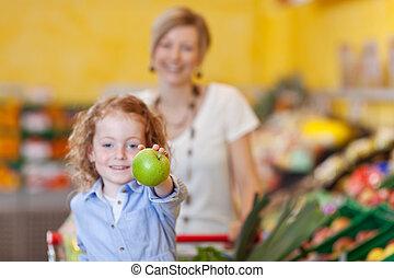 menina, mostrando, maçã, com, mãe, em, fundo, em, loja