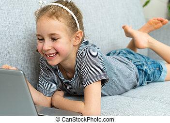 menina pequena sorrindo, sofá, com, laptop.