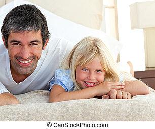 menina pequena sorrindo, tendo divertimento, com, dela, pai, encontrar-se cama