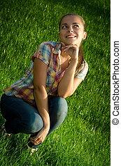 menina, prado verde, sentando