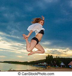 menina, pular, praia, em, pôr do sol, experiência., feliz, menina, pular, praia, ligado, a, alvorada, time., a, conceito, de, liberdade, e, alegria