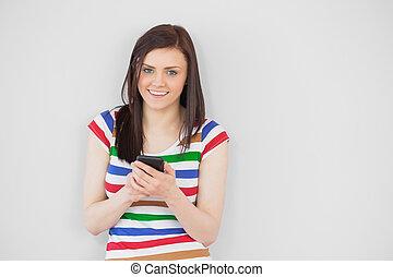 menina sorridente, usando, dela, telefone móvel, olhando câmera