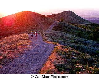 meninas, hiking, ao longo, um, montanha, em, amanhecer, ou, pôr do sol