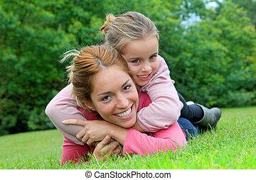 menininha, e, mãe, deitando, ligado, capim, parque