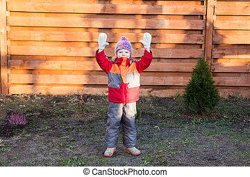 menininha, levanta, dela, mãos cima, contra, cerca madeira