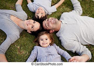 menininha, mentindo, em, um, parque, com, dela, pais, e, irmão