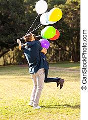 menino adolescente, abraçando, ao ar livre, namorada, feliz