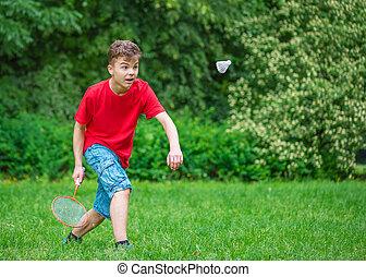 menino adolescente, badminton, parque, tocando