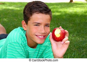 menino, adolescente, comer, maçã vermelha, ligado, jardim, capim