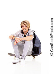 menino adolescente, feliz, skateboard, sentando