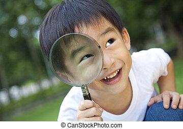 menino, asiático, segurando, magnifier
