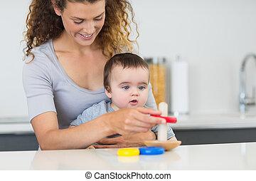 menino bebê, olhar, mãe jogando, com, brinquedos