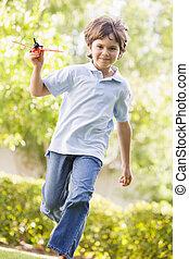 menino, brinquedo, jovem, executando, ao ar livre, avião, sorrindo