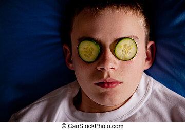 menino, cama, com, fatias pepino, sobre, seu, olhos
