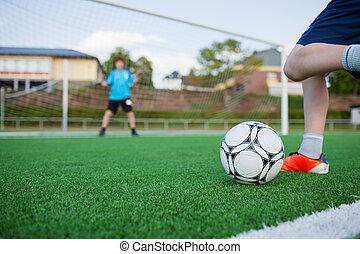 menino, chutando, bola futebol, com, goleiro, em, fundo