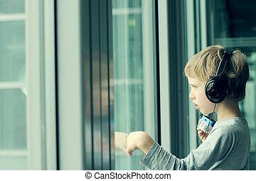 menino, com, fones, olhar, a, janela, em, a, aeroporto