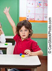 menino, com, mão levantada, sentando escrivaninha