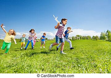 menino, crianças, muitos, executando, brinquedo, segurando, avião