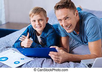 menino, estudar, mostrando, pai, cima, enquanto, polegares, sorrindo