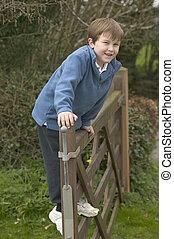 menino, feliz, portão
