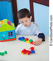 menino, jogar brinquedos, escrivaninha, em, pré-escolar