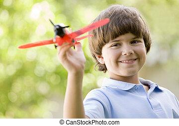 menino jovem, com, avião brinquedo, ao ar livre, sorrindo