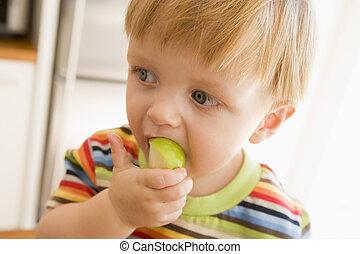 menino jovem, comendo maçã, dentro