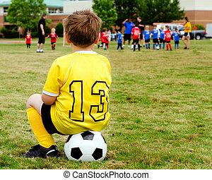 menino jovem, criança, em, uniforme, observar, organizado, juventude, futebol, ou, jogo football, de, sidelines