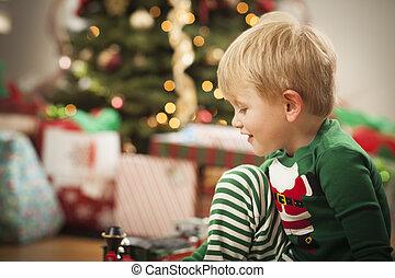menino jovem, desfrutando, manhã natal, perto, a, árvore