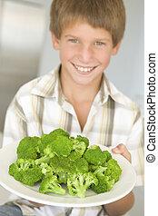 menino jovem, em, cozinha, comer, brócolos, sorrindo