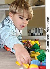 menino jovem, jogar brinquedos