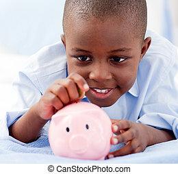 menino jovem, ligado, um, cama, pôr, dinheiro, em, um, cofre