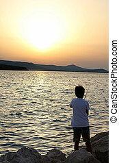 menino jovem, pesca, em, pôr do sol