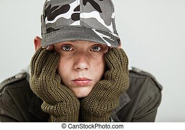 menino jovem, pouting, enquanto, segurando, rosto, em, luvas