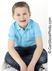 menino jovem, sentando, em, estúdio