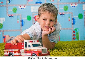 menino jovem, tocando, com, car, tapete