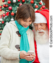 menino, mostrando, smartphone, para, papai noel