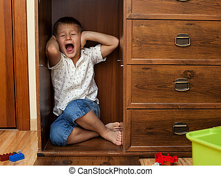 Menino, pequeno, armário, chorando, escondendo