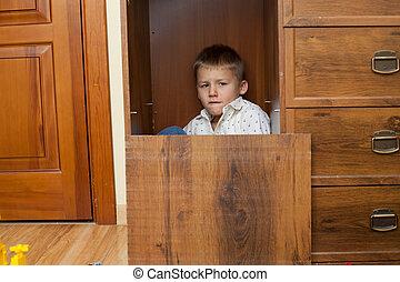 Menino, pequeno, armário, escondendo