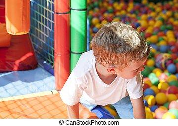 menino, pequeno, bolas, coloridos, pátio recreio, tocando