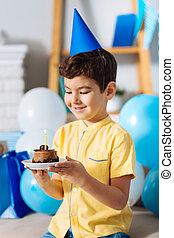 menino, pequeno, seu, aniversário, segurando, bolo, chapéu partido