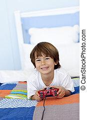 menino, pequeno, seu, cama, videogames, sorrindo, tocando, mentindo