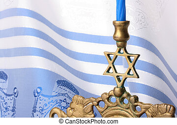 Menorah in front of a blue and white tallit. Add your text...