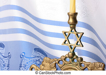Menorah standing in front of a blue and white tallit. Add...