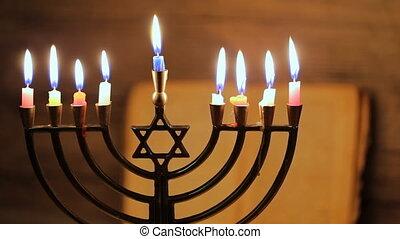 Menorah with candles for Hanukkah against defocused lights,...