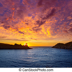 Menorca sunset in Cala Morell at Ses torretes beach Balearic...