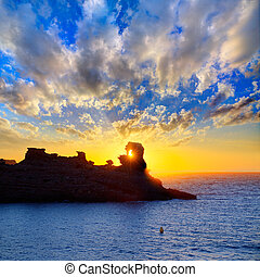 Menorca sunset in Cala Morell at Ses torretes beach Balearic...