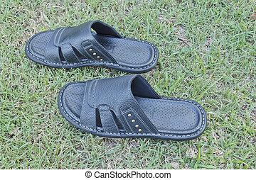 Men's black sandals on the grass