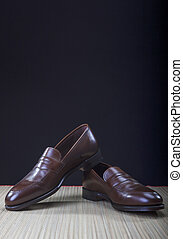 Mens Brown Penny Loafer Shoes Against Black Background