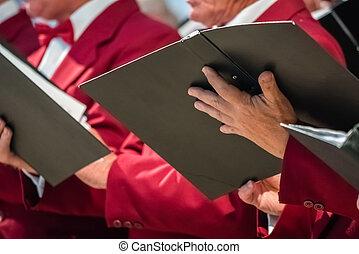 Mens choir members holding singing book - Close up of mens...